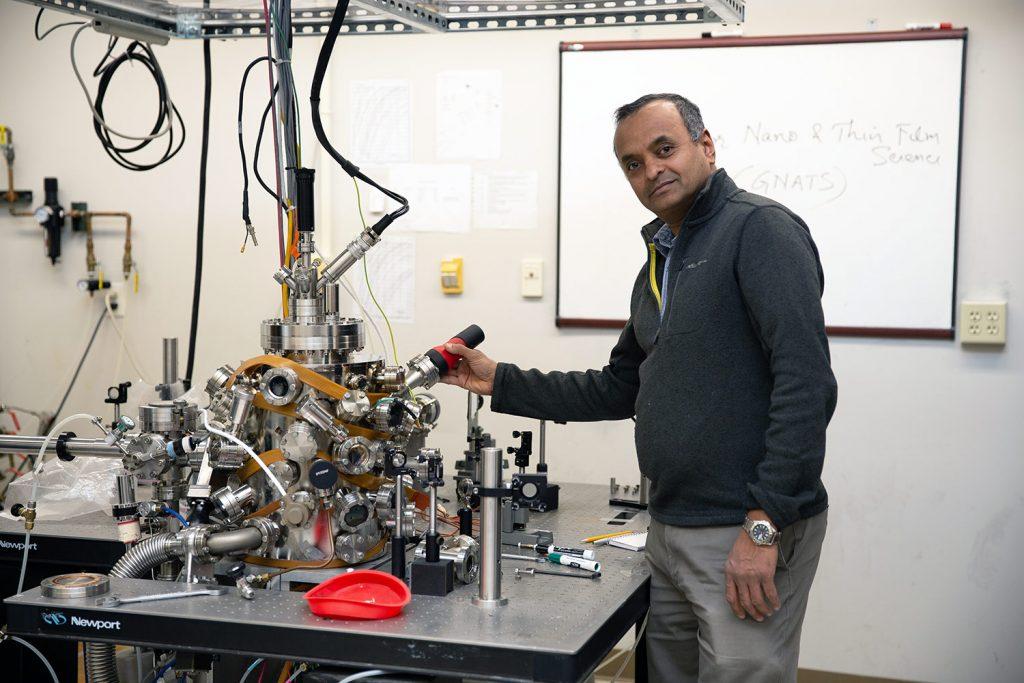 Ramki Kalyanaraman holds a tool in a laboratory.