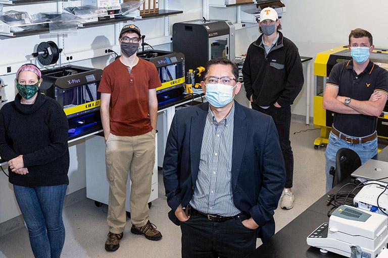 Rigoberto Advincula stands with several students in his laboratory.